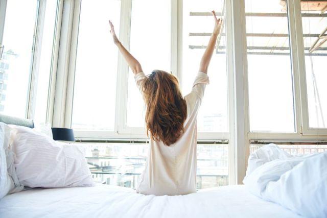 Frau steht aus Bett auf