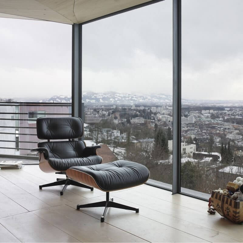 Eames Lounge Chair mit Ottoman vor Glasfront